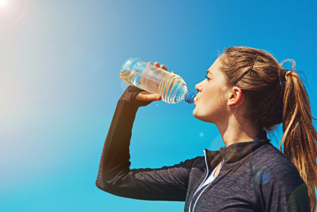 Shot of a sporty young woman drinking water outdoors